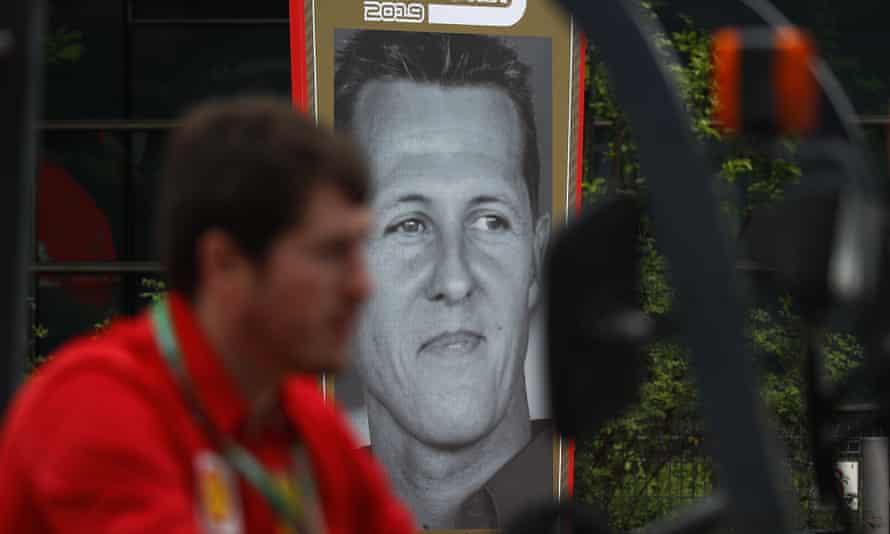 A Ferrari team crew member drives a forklift past a poster of former F1 champion Michael Schumacher.