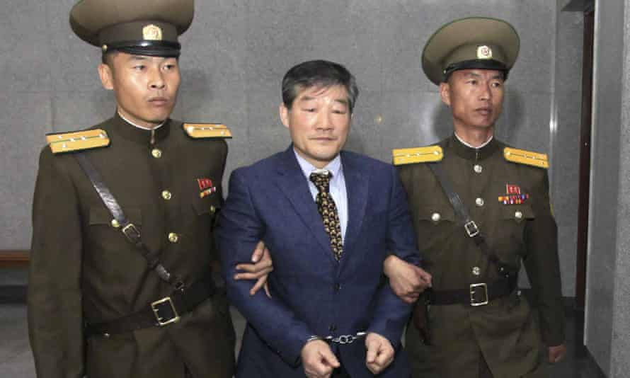 Kim Dong Chul is escorted to his trial in Pyongyang on Friday. He was found guilty of spying.
