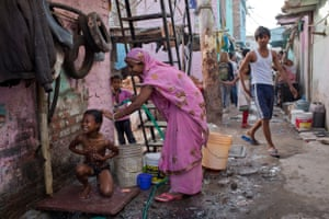 Sita Devi washes her son in one of the streets that runs through Safeda Basti, Delhi, India, April 2015