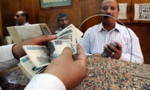 An employee counts Egyptian pounds in a bank in Cairo