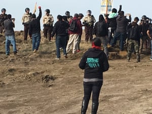 Demonstrators at the Dakota Access pipeline cheer as armed soldiers and law enforcement officers move in to force protesters off the land