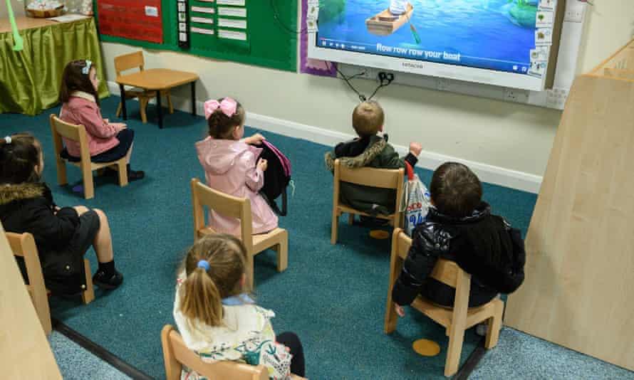 Nursery children sit apart from each other.