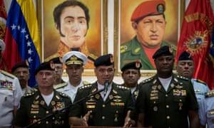 The Venezuelan defense minister, Vladimir Padrino López, center, denounces US sanctions against four service men on Saturday in front of portraits of Simón Bolívar and Hugo Chávez.