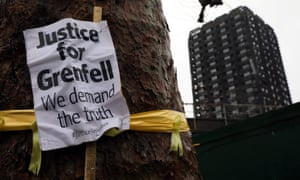 A 'Justice for Grenfell' sign hangs on a tree near the tower.