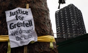 A 'Justice for Grenfell' sign hangs on a tree near Grenfell Tower