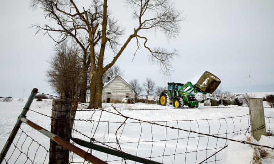 Farmer Jon Shelley moves bales of hay to feed cows in front of an abandoned school house.