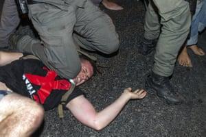 A police officer kneels on a demonstrator's neck