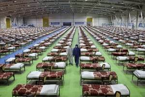 People in protective clothing walk past rows of beds at a temporary 2,000-bed hospital for coronavirus patients set up by the Iranian army at the international exhibition centre in northern Tehran
