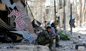 A Syrian government soldier sits in the rubble of a building in Douma on the outskirts of Damascus on 16 April 2018 during an organised media tour after the Syrian army declared that all anti-regime forces have left eastern Ghouta