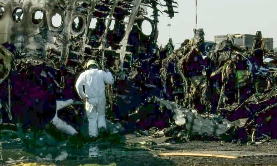 Investigators study the charred wreckage of the Sukhoi Superjet 100