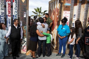 Members of the Hernández family hug each other as a gate is opened for a few minutes at the US-Mexico border.