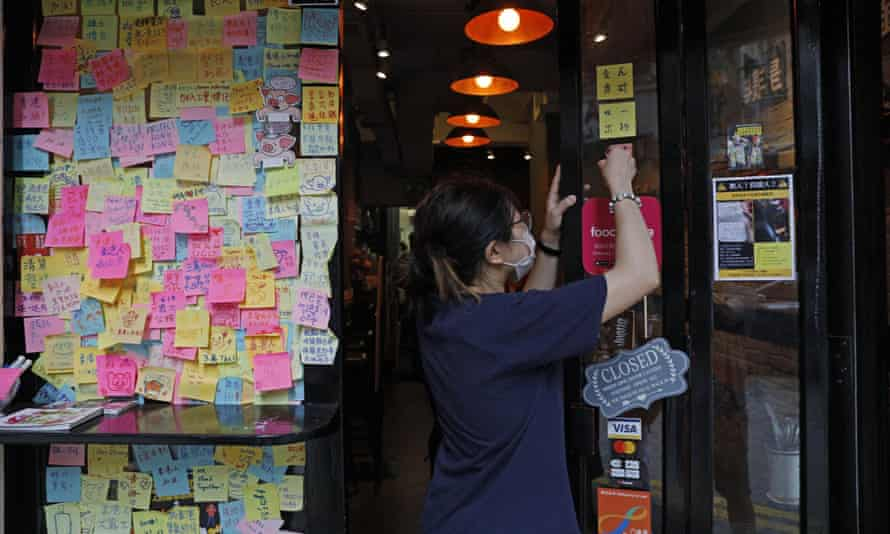 An employee removes stickers and posters with messages in support of the pro-democracy movement at a restaurant in Hong Kong.