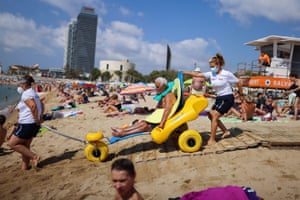 Barcelona, Spain: Manuel Molina, 80, sits on an amphibious chair as he is helped by lifeguards before swimming in the Mediterranean, on Barcelona's Nova Icària beach