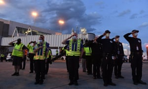 Transportation Security Administration agents and Denver paramedics salute as the casket carrying the body of retired paramedic Paul Cary arrives at Denver International Airport on Sunday.