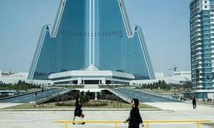 "Women walk in front of the unfinished Ryugyong hotel. The tallest building in the North Korean capital, it has been under construction for over thirty years but no opening date is set. It has been nicknamed the ""hotel of doom"". Pyongyang, North Korea."