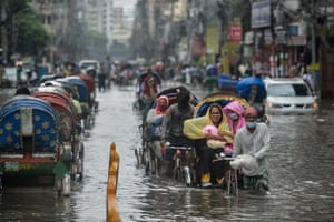 Dhaka, India: Rickshaws are pulled through a waterlogged street along with their passengers after a heavy downpour.