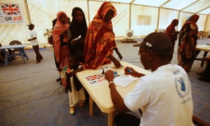 UK aid officials administer a cash assistance project implemented by the World Food Programme at a UN refugee camp in the city of Nyala, in the Sudanese state of South Darfur