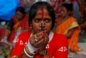 Kolkata, India: A woman worships the Hindu goddess Bipodtarini during a ceremony in which married women fast for a whole day for the betterment of their family