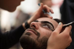 Muhammad Ali, from Afghanistan, has make-up applied for his role as a model