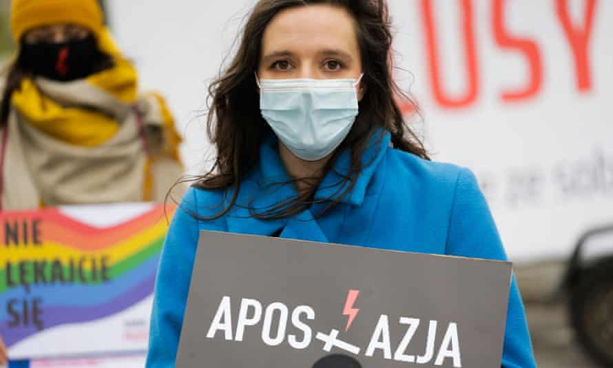 A woman hold a poster urging people to commit formal acts of apostasy to renounce their faith.