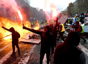 People holding flares and wearing masks emerge onto the Champs Élysées as the evening draws.
