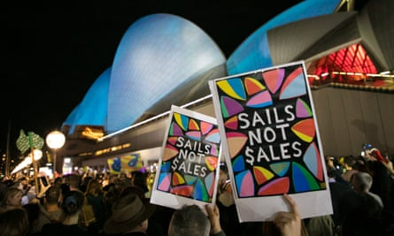 Protesters hold placards next to the Sydney Opera House after an ad for the Everest Cup horse race was projected on to it.