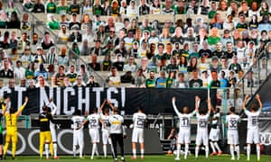 Borussia Mönchengladbach players celebrate in front of cardboard cutouts.