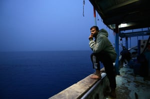 One of the crew looks out to sea