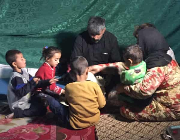 The Al-Eid family eating lunch in their tent.