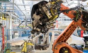 A robot mounts a cockpit into a Mercedes-Benz S-Class car on the assembly line in Stuttgart.