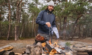 chef Niklas Ekstedt cooking meat over a wood fire in a clearing on Fjäderholmarna.