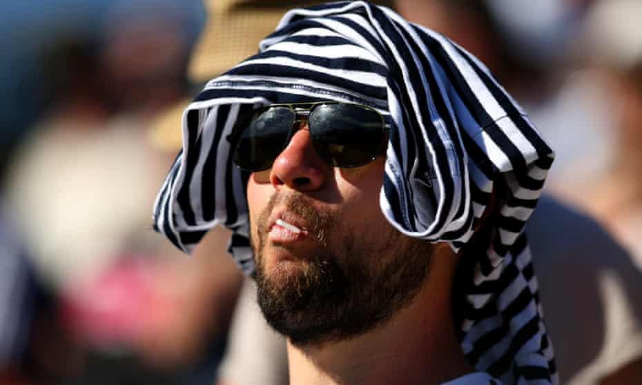 A spectator shields himself from the heat at Wimbledon.