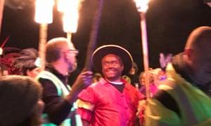 Trevor Bryant wears blackface as he follows a Caribbean-themed float at Saturday's bonfire night celebration.