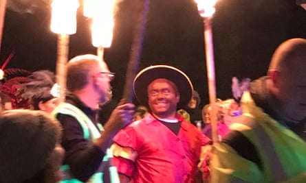 Trevor Bryant wears blackface as he follows a Caribbean-themed float at Saturday's bonfire night celebration.
