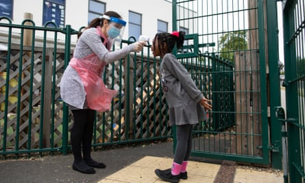 A member of staff takes a child's temperature at the Harris Academy's Shortland's school in London on 4 June.
