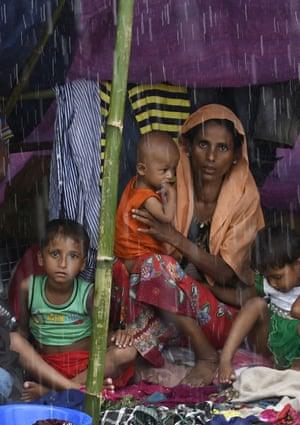 Rohingya Muslim refugees protect themselves from rain in Balukhali refugee camp near the Bangladesh town of Gumdhum.