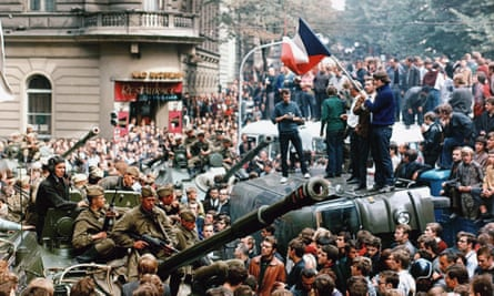 Czech youngsters holding a Czechoslovak flag stand atop an overturned truck as other Prague residents surround Soviet tanks in Prague, 21 August 1968.