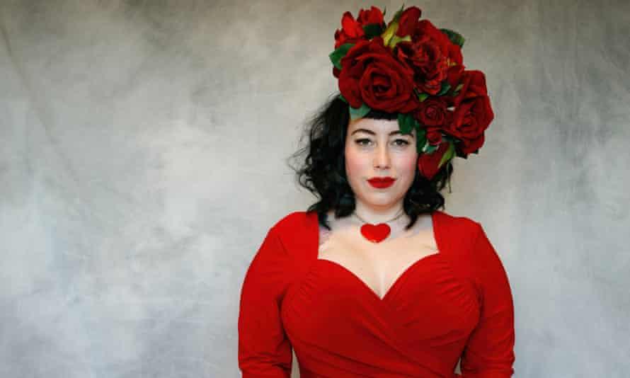 Bink wearing a large velvet rose fascinator, heart necklace and low-cut dress, slightly smiling