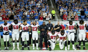 Members of the Atlanta Falcons football team Grady Jarrett and Dontari Poe take a knee during the playing of the national anthem.