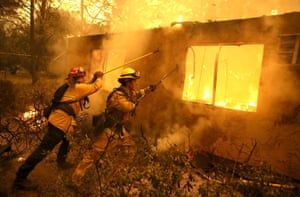 Firefighters try to keep flames from a home from spreading to a neighbouring apartment complex. Fuelled by high winds and low humidity, the rapidly spreading fire ripped through the town of Paradise and 70,000 acres, destroying homes and businesses in a matter of hours