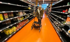 A older woman in a supermarket aisle