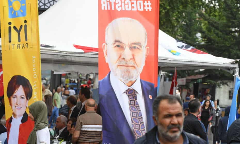 People walk in front of banners of two of Turkey's presidential candidates – Temel Karamollaoğlu, right, and Meral Aksener, left