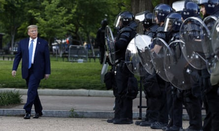 Donald Trump walks past police in Lafayette Park after he visited outside St John's Church across from the White House on Monday.