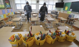 Workers disinfect as a precaution against the new coronavirus ahead of school reopening in a class at an elementary school in Gwangju, South Korea, Tuesday, 26 May 2020.