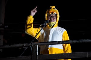 Anon Nampa, a protest leader, wears a duck costume while addressing a demonstration. Thousands gathered outside the headquarters of Siam Commercial Bank to demand King Maha Vajiralongkorn give royal assets to the people.
