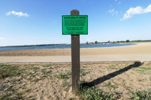 A water quality notice sign hangs near the beach at Big Creek state park, in Polk City, Iowa.