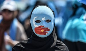 A demonstrator wearing a mask painted with the colours of the flag of East Turkestan and a hand bearing the colours of the Chinese flag attends a protest of supporters of the mostly Muslim Uighur minority and Turkish nationalists to denounce China's treatment of ethnic Uighur Muslims during a deadly riot in July 2009 in Urumqi, in front of the Chinese consulate in Istanbul, on July 5, 2018. - Nearly 200 people died during a series of violent riots that broke out on July 5, 2009 over several days in Urumqi, the capital city of the Xinjiang Uyghur Autonomous Region, in northwestern China, between Uyghurs and Han people. (Photo by OZAN KOSE / AFP)        (Photo credit should read OZAN KOSE/AFP/Getty Images)
