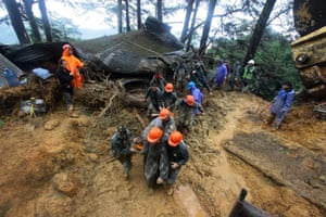 Rescuers carry a victim of a mudslide in Baguio City, the Philippines