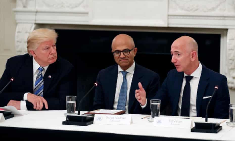 Microsoft CEO Satya Nadella sits between Donald Trump and Jeff Bezos at a White House meeting last year.