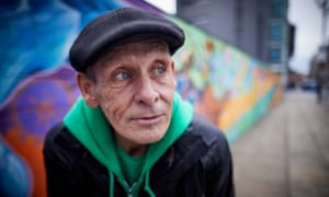 Danny Collins, who was homeless, stands next to graffiti art painted by homeless people in Manchester.